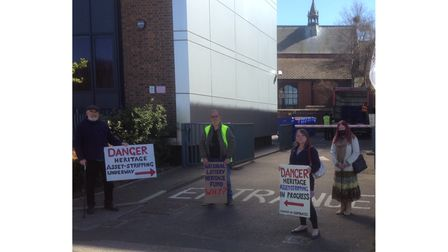 Members of the SORO group wave placards as Lowestoft Record Office archives are moved to The Hold in Ipswich.