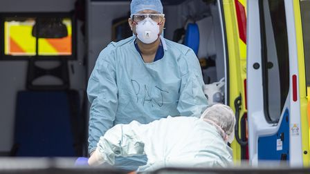 NHS workers in PPE take a patient with an unknown condition from an ambulance at St Thomas' Hospital