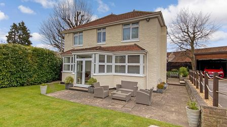 Detached house in High Street, Nailsea, with cream render, white window frames, patio and lawn in front.