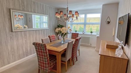 Beige dining room with wooden table and beige and red tartan covered chairs, sideboard, mirror on left and window at back.
