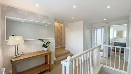 landing with leaf-patterned wallpaper, side table with mirror above on left, white banisters on right and doors at the back.