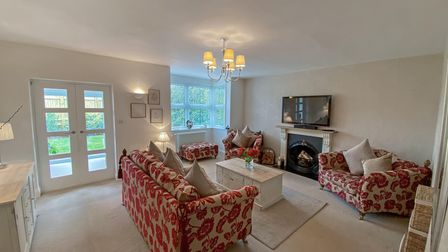 Large beige living room with French doors on right with bay window next to it. Beige and red sofas, fireplace with TV over.