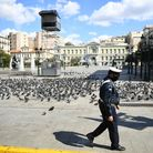 A police officer walks past an empty square in the centre of Athens, Greece, during lockdown