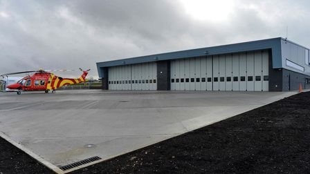A concrete apron with a hangar in the background. To the left: a red helicopter with painted yellow swirls.