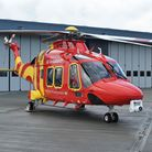 A red helicopter with a camera on the front parked in front of a hangar: Essex and Herts Air Ambulance
