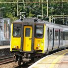 A train with a bright yellow front pulling into a platform