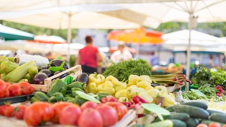 Farmers' food market stall with variety of organic vegetable. Vendor serving and chating with custom