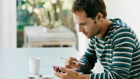 Young man considering investments and finances on his smartphone