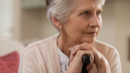 Serious senior woman sitting on couch holding walking stick and looking away. Portrait of thoughtful