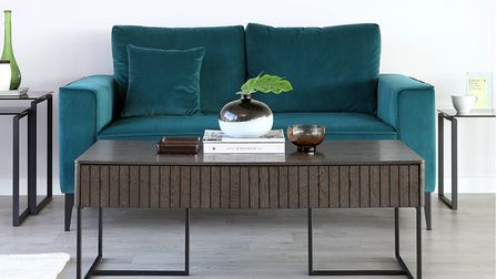 A livingroom interiors with teal sofa and brown coffee table in Japandi style.
