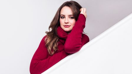 A woman in a red jumper against a plain white background