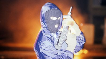 A Provisional IRA gunman stands with his automatic assault rifle and a mask in Bogside, Derry, inAugust 1986