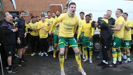 Kenny McLean of Norwich and the Norwich players celebrate outside the ground with the gathered fans