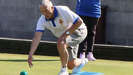 Barrie Forse in bowling action during the Men v Ladies match at St Andrews, watched by Beccy McMillan