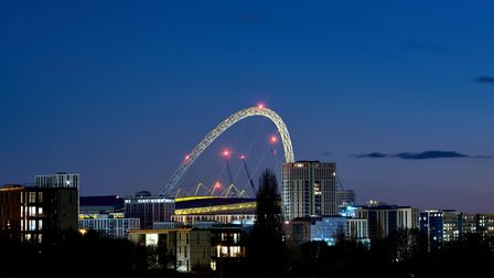 A view of Wembley stadium in London, with the arch illuminated at dusk. Picture date: Monday April 5
