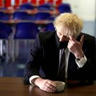 Prime Minister Boris Johnson speak with pupils after taking part in a science lesson during a visit