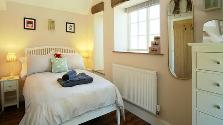 A double bed with blue cushion and white duvet and pillow cases