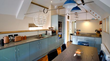 A kitchen with dark blue light shades and duck egg blue glossy cupboards