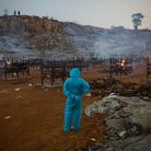 A man watches mass cremations in a disused granite quarry repurposed to cremate the Covid dead inBengaluru, India