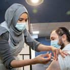 Pharmacist Aisha Noor vaccinates Eliahu Lopez at the Golders Green Hippodrome