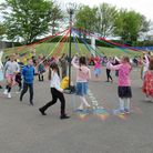 A group of children stand in a circle. They are holding a coloured string attached to a central pole (the maypole).