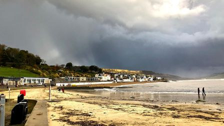 A stretch of sand leads to Lyme Regis on the coast