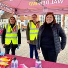 Three people, two of whom are in Hi-Vis, stand under a gazebo
