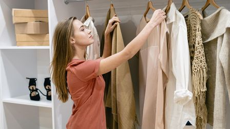 Young woman living in London checking clothes for moths