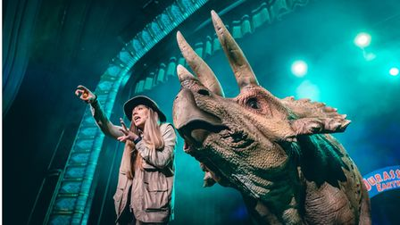 Woman with huge dinosaur puppet in Jurassic Earth Live show
