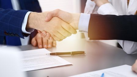 Business people shaking hands, finishing up a papers signing. Meeting, agreement and lawyer consulti