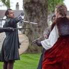 Actors perform sword fight in Shakespeare history play for open air theater production.