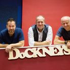 Band memebers of The Dockneys stand behind a sign which reads Dockneys and infront of a blue and red background