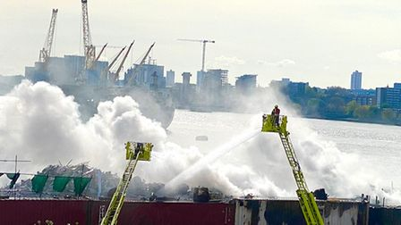 Crews work to extinguish the huge blaze that broke out in a scrap yard by the River Thames in Silvertown.