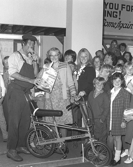 Jack Douglas, dressed in dungarees and a cap and holding a box of shredded wheat, at Hollis Cycles in 1971.