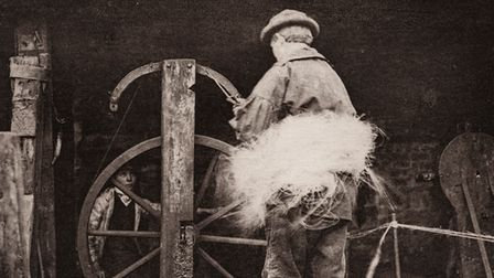 An old photograph of a man with hay.