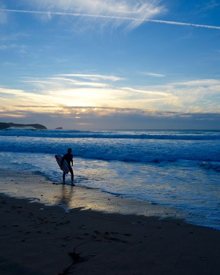 Surfer leaves the beach at Fistral beach at sunset