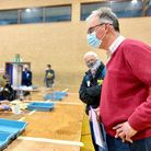 A man in a red sweater stands over a table. On it, ballots are being counted