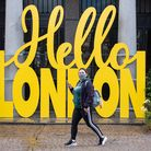 A woman wearing a face mask passes a 'Hello London' sign in Covent Garden, London, following the fur