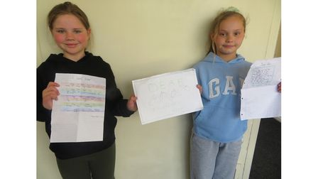 Amber and Chloe with the poems they wrote for Deaf Awareness Week