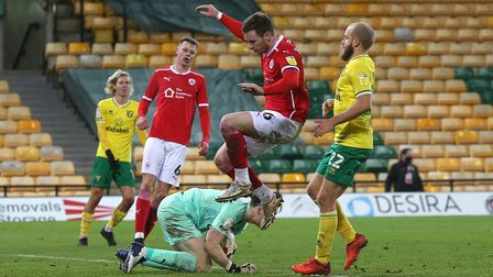Jack Walton of Barnsley saves at the feet of Michael Sollbauer and Teemu Pukki of Norwich
