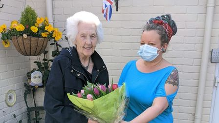 Jantje Huggins being presented with Dutch tulips by Aimee Davey, at Spring Lodge care home in Woolverstone