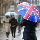 A man carries a Union flag umbrella