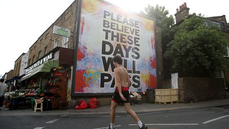 A man walks past a large billboard reading 'Believe me, these days will pass' at London Fields on Ma
