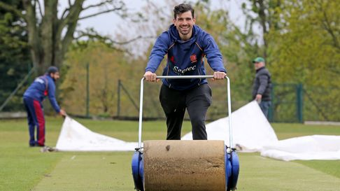 Joe Ellis-Grewal of Wanstead attempts to dry out the wicket after heavy rain ahead of their clash with Hornchurch