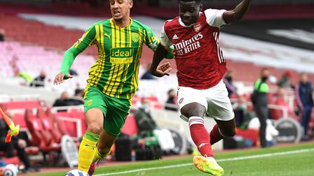 West Bromwich Albion's Callum Robinson (left) and Arsenal's Bukayo Saka battle for the ball during t