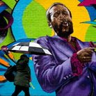 A woman walks past local artist Aniekan Udofia's mural of Marvin Gaye in Washington, DC