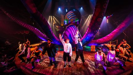 Actors onstage at the Great Yarmouth hippodrome with a giant octopus behind them.