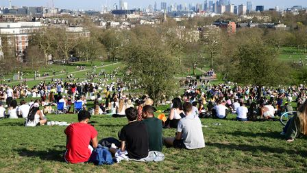 People enjoy the warm weather and sunshine on Primrose Hill in north London. Picture date: Tuesday M
