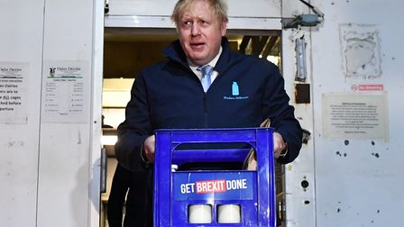 Boris Johnson carries a crate of milk on the final day of campaigning beforethe 2019 general election