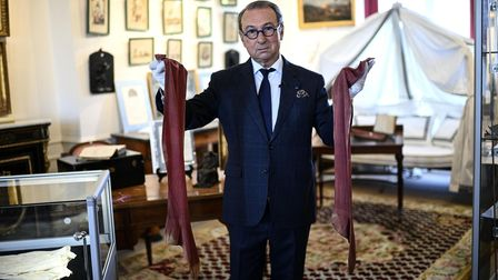 Auctioneer Jean-Pierre Osenat holds a pair of stockings that belonged to Napoleon